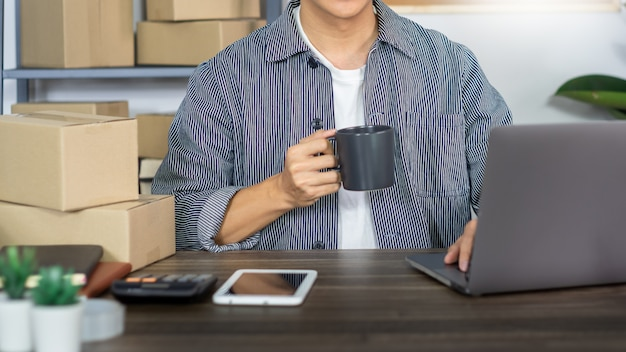 Hombre asiático empresario emprendedor emprendedor de pequeñas empresas sme hombre independiente que trabaja con la caja para el marketing en línea y la escena de entrega en la oficina en casa, concepto de vendedor de negocios en línea