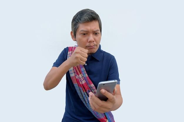 Hombre asiático enojado golpeando su teléfono
