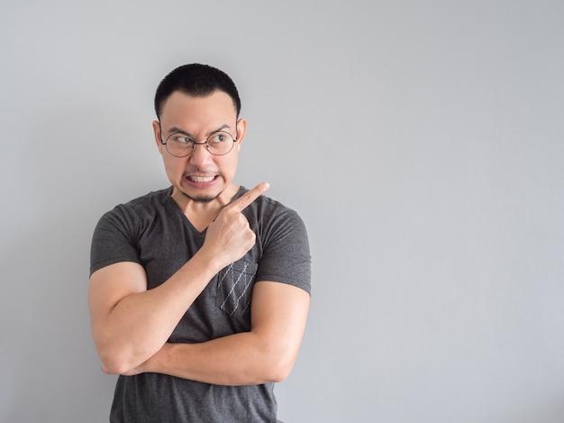 Hombre asiático enojado y loco en estilo de pelo negro de la camiseta y del skinhead.