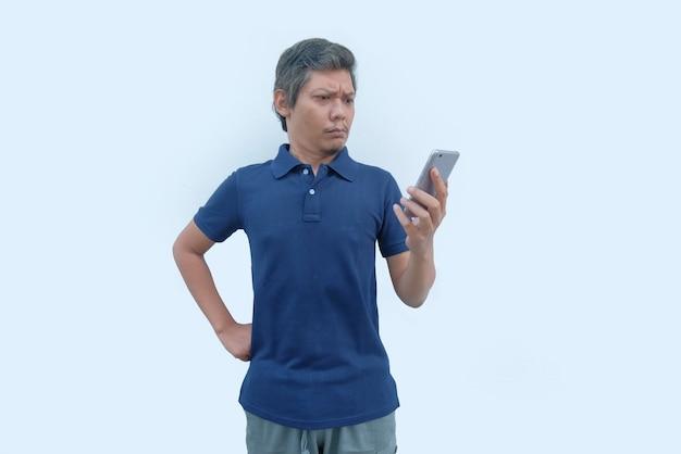 Hombre asiático enojado mirando la pantalla del teléfono