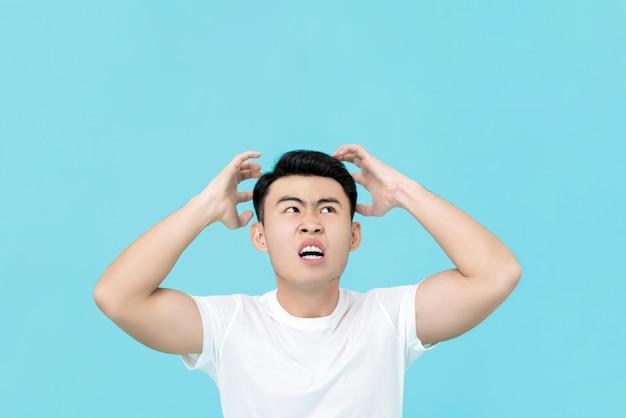 Hombre asiático enojado molesto con las manos apretando la cabeza