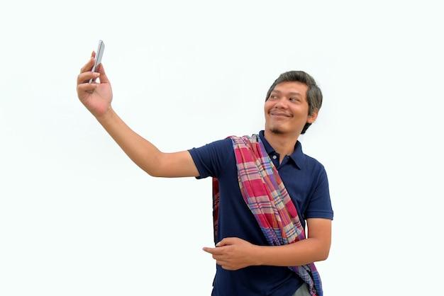 Hombre asiático enojado señalando la pantalla del teléfono