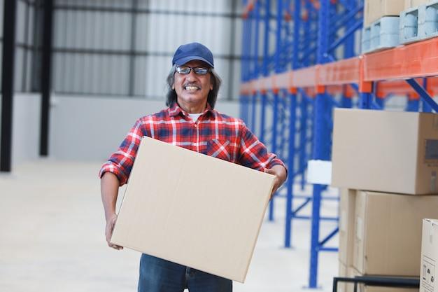 Hombre asiático entrega buena caja al cliente en fábrica y firma en tableta sonrisa y buen servicio, concepto logístico de compras en línea