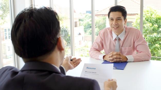Hombre asiático en entrevista de trabajo en el fondo de la oficina