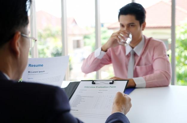Hombre asiático en entrevista de trabajo en la oficina, joven hombre de negocios asiático mientras entrevista para reclutamiento, búsqueda de empleo, negocios