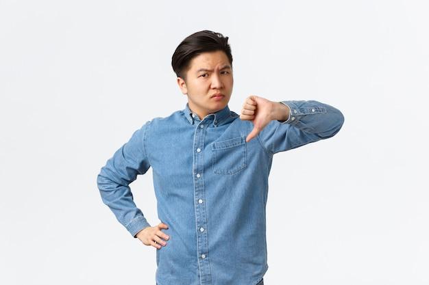 Hombre asiático escéptico decepcionado que parece crítico y sin gracia, de pie fondo blanco sacudiendo la cabeza y mostrando el pulgar hacia abajo en desaprobación, disgusto y no recomiendo algo