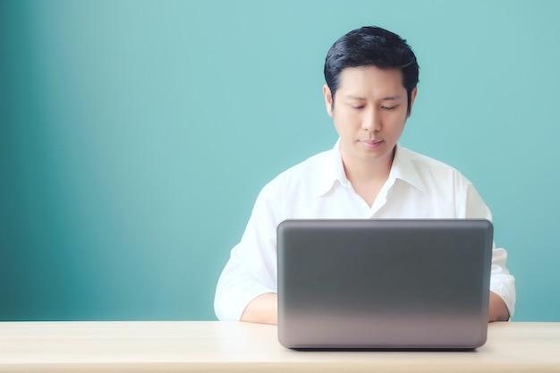 Hombre asiático escribiendo la computadora portátil en el escritorio de la oficina con espacio para texto, poeple y concepto de tecnología