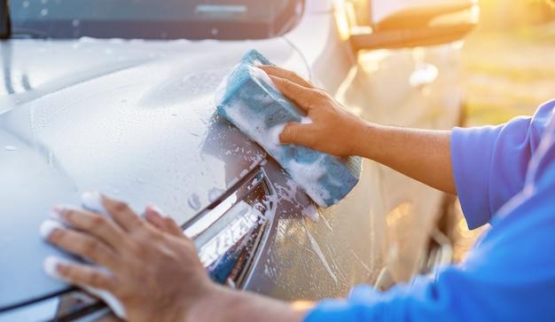 Hombre asiático con esponja azul con jabón para lavar el automóvil al aire libre en la hora del atardecer