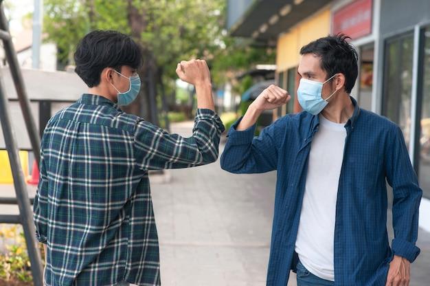 Hombre asiático estrechar la mano sin concepto táctil nuevo distanciamiento social normal, puerta exterior