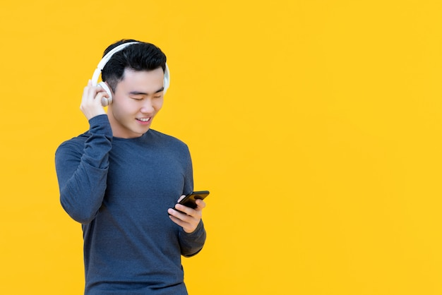 Hombre asiático feliz con auriculares escuchando música en streaming desde el teléfono smarrt
