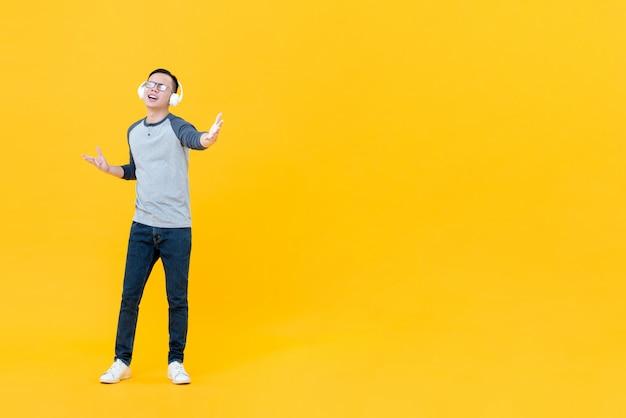 Hombre asiático feliz disfrutaba escuchando música con auriculares
