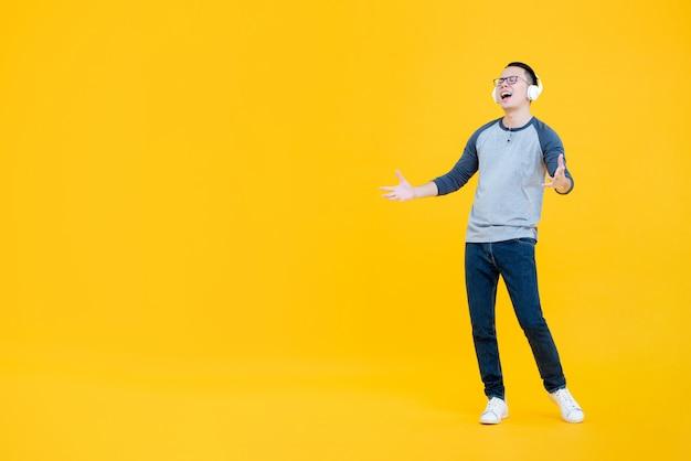 Hombre asiático feliz escuchando música con auriculares