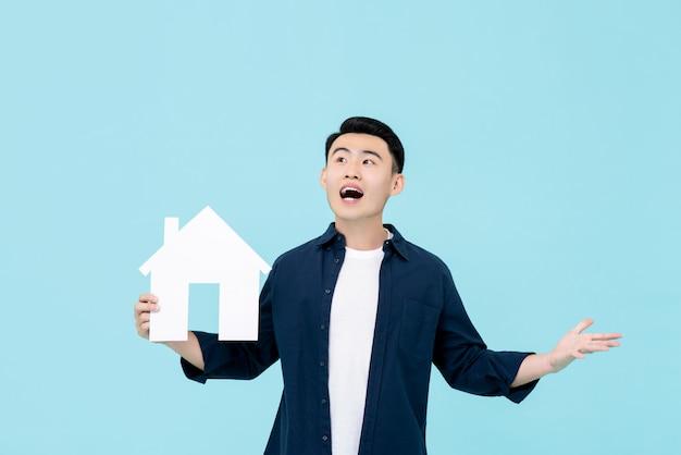 Hombre asiático feliz joven que mira la sorpresa que sostiene el modelo de la casa para los conceptos de la propiedad