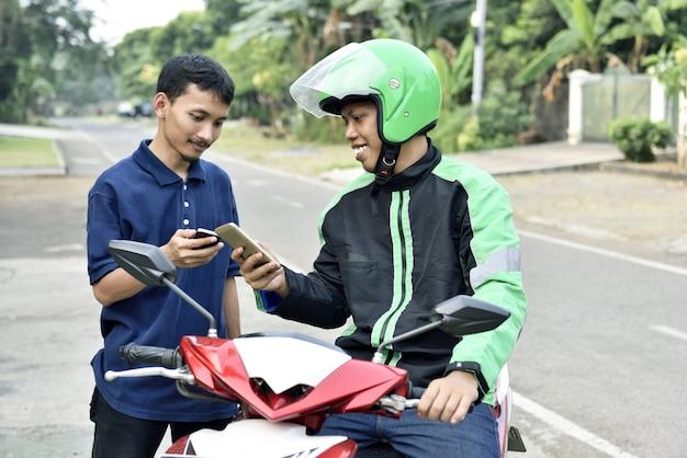 Hombre asiático feliz que pide el taxi de la motocicleta por el teléfono móvil