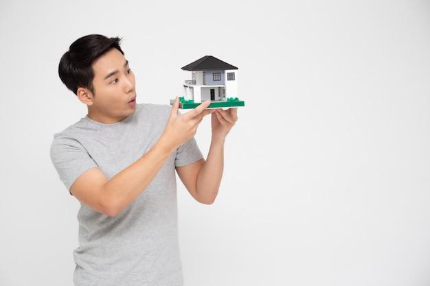 Hombre asiático feliz que sostiene el modelo casero, planea tomar un préstamo grande para el concepto de la casa de compra