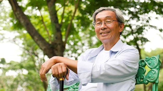 Hombre asiático feliz sentado en un banco en el parque.