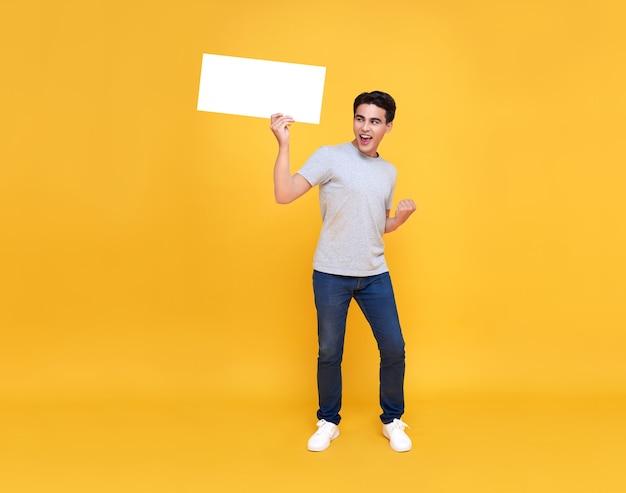 Hombre asiático feliz sonriente que sostiene las burbujas del discurso en blanco sobre fondo amarillo.