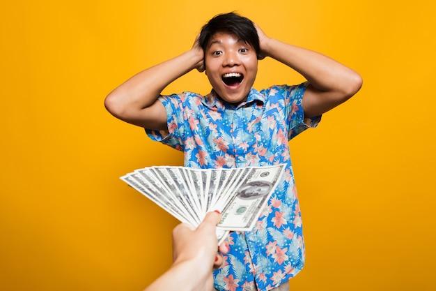 Hombre asiático feliz sorprendido recibiendo billetes de dinero