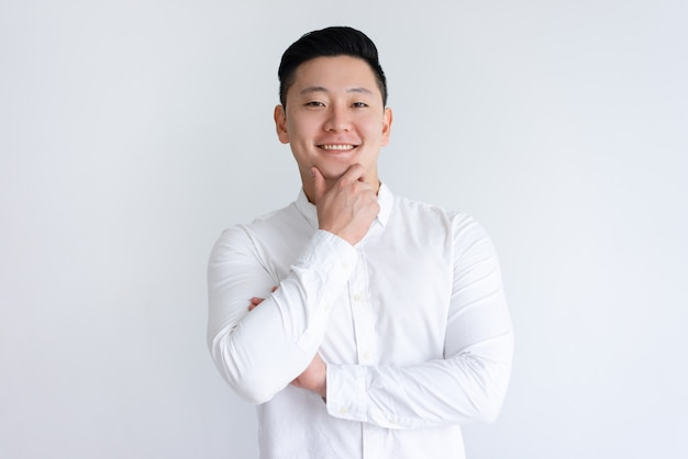 Hombre asiático feliz tocando la barbilla y mirando a cámara