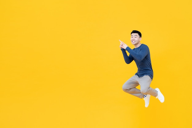 Hombre asiático flotando en el aire apuntando con dos dedos al espacio vacío