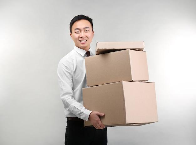 Hombre asiático guapo con cajas de cartón en superficie clara