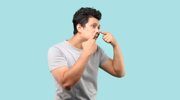 Hombre asiático guapo tocando su rostro, exprimiendo la espinilla