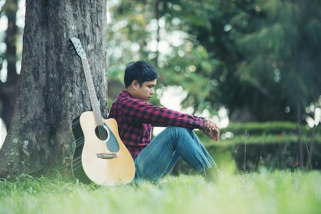 Hombre asiático con guitarra acústica en un parque