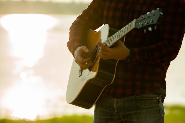 Hombre asiático con guitarra acústica durante una puesta de sol