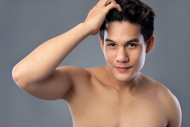 Hombre asiático hamdsome joven descamisado con la cara radiante limpia