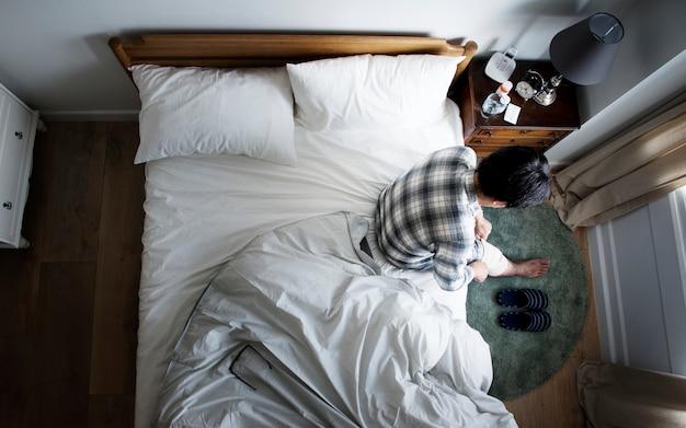 Hombre asiático herido sentado en la cama