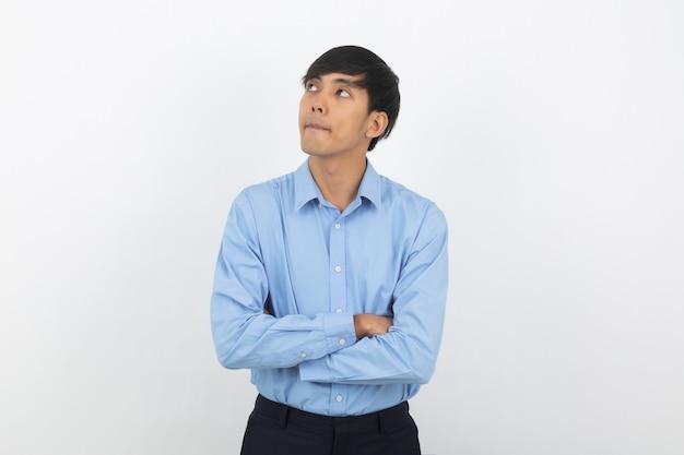 Hombre asiático hermoso joven que piensa una idea mientras que mira para arriba con los brazos cruzados