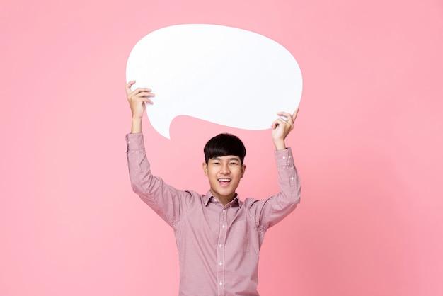 Hombre asiático hermoso joven sonriente feliz que lleva a cabo la burbuja del discurso