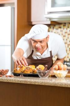 Hombre asiático hornear magdalenas en la cocina de casa