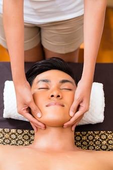 Hombre asiático indonesio en wellness spa de belleza con aromaterapia, masaje facial con aceite esencial, mirando relajado