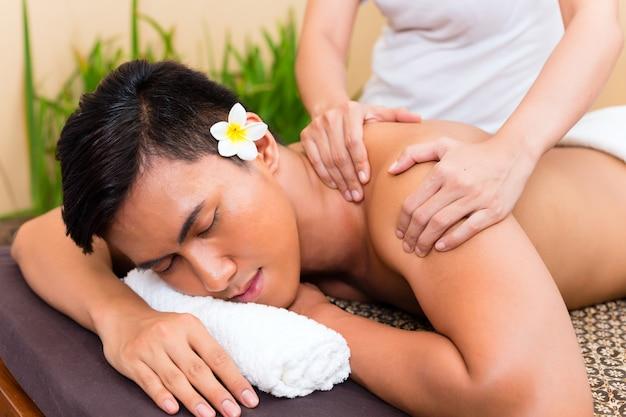 Hombre asiático indonesio en wellness spa de belleza con masaje de aromaterapia con aceite esencial, mirando relajado