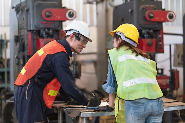 Hombre asiático ingeniero explicando mujer ingeniera máquina de inspección en línea de producción en una fábrica industrial