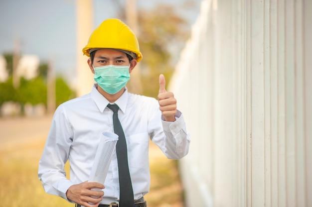 Hombre asiático ingeniero uso mascarilla amarillo casco con blueprint inspección construcción edificio finca