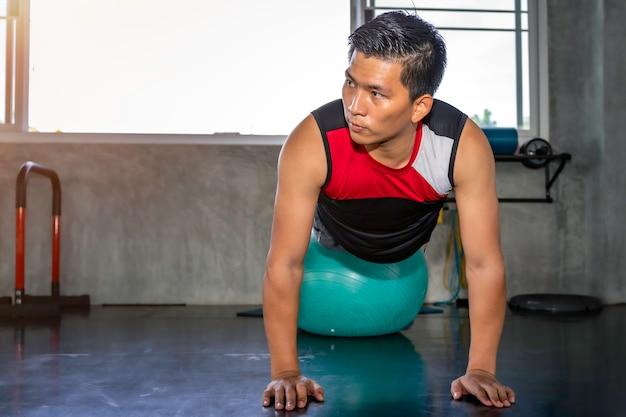 Hombre asiático inteligente en ropa deportiva entrenamiento músculos abdominales con gimnasio de pelota en fitness.