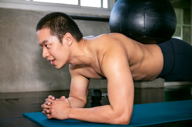Hombre asiático inteligente en ropa deportiva entrenamiento músculos abdominales con tablas en el gimnasio