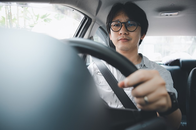 Hombre asiático joven hermoso que usa el cinturón de seguridad mientras conduce un coche