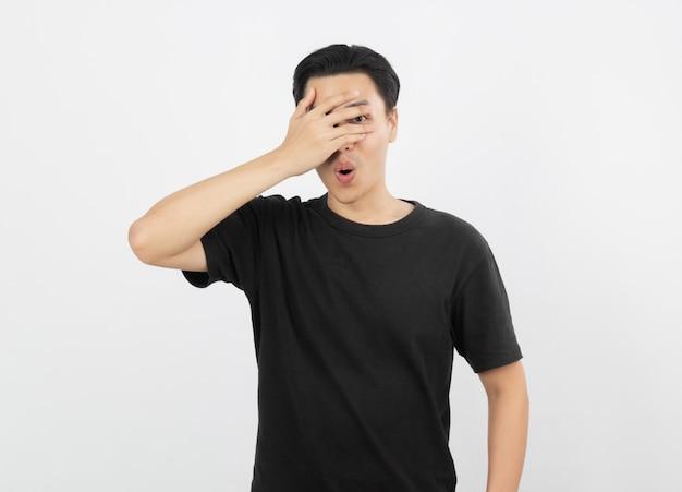 Hombre asiático joven hermoso sobre el fondo aislado que cubre ojos y que mira a través de los dedos.