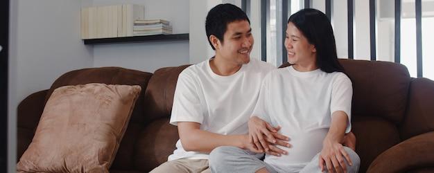 El hombre asiático joven de la pareja embarazada toca el vientre de su esposa hablando con su hijo. mamá y papá se sienten felices sonriendo pacíficos mientras cuidan bebé, embarazo acostado en el sofá en la sala de estar en casa.