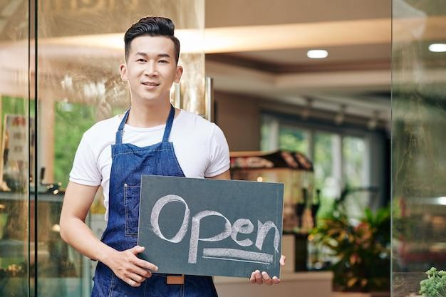 Hombre asiático joven positivo de pie en la entrada del café con cartel abierto
