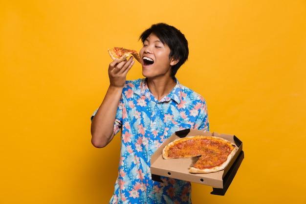 Hombre asiático joven que se encuentra aislado sobre el espacio amarillo comer pizza.