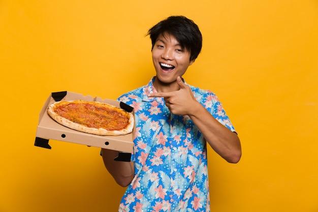 Hombre asiático joven que se encuentra aislado sobre el espacio amarillo sosteniendo pizza apuntando.