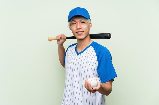 Hombre asiático joven que juega a béisbol sobre verde aislado
