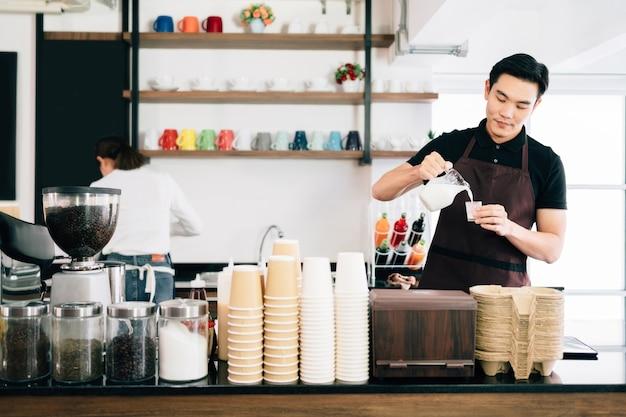 Hombre asiático joven que mide la leche para hacer café con leche y el dueño de la cafetería barista de pie dentro del mostrador de café.