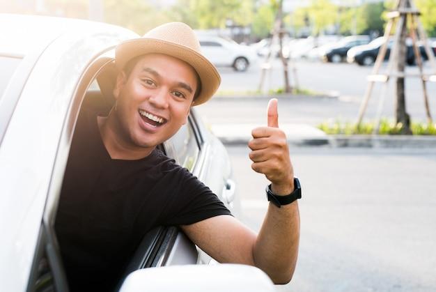 Hombre asiático joven que muestra los pulgares para arriba mientras conduce el coche