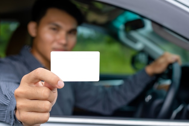 Hombre asiático joven que se sienta en el coche moderno y que sostiene la tarjeta de visita en blanco