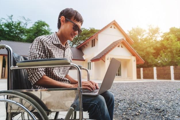 Hombre asiático joven que se sienta en una silla de ruedas y que trabaja en su computadora portátil.